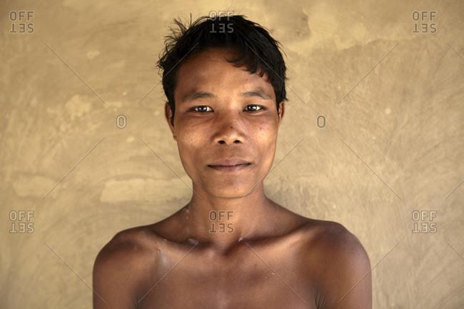 Garo Line Para Village, Sreemangal, Bangladesh - May 2, 2013: Portrait of a Garo tribal boy against a yellow wall