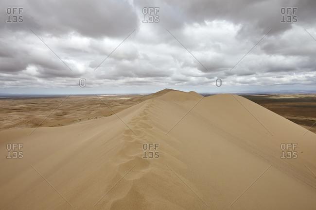 Panoramic view of the Khongoryn Els sand dunes under cloudy skies in Gobi Desert, Mongolia