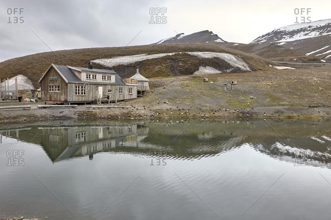Longyearbyen, Spitsbergen, Svalbard, Norway - June 26, 2014: Wooden house nearby a beautiful arctic lake in summertime at Arctic Bay near Longyearbyen