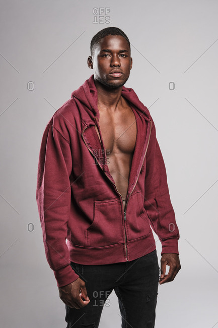 Black fitness man wearing a red hoodie and black trousers on a grey background
