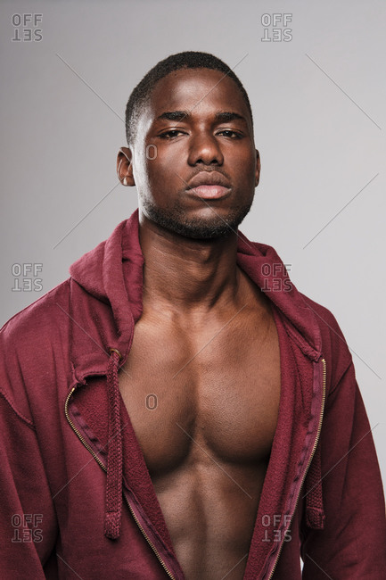 Close up portrait of a black fitness man wearing a red hoodie