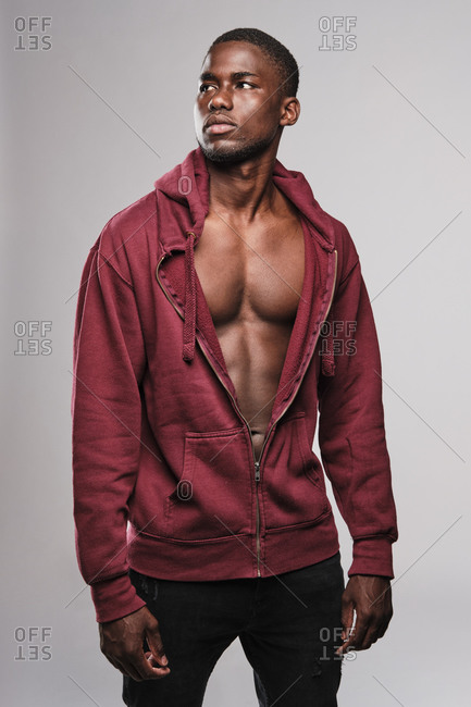 Black man wearing a red hoodie and looking to the right