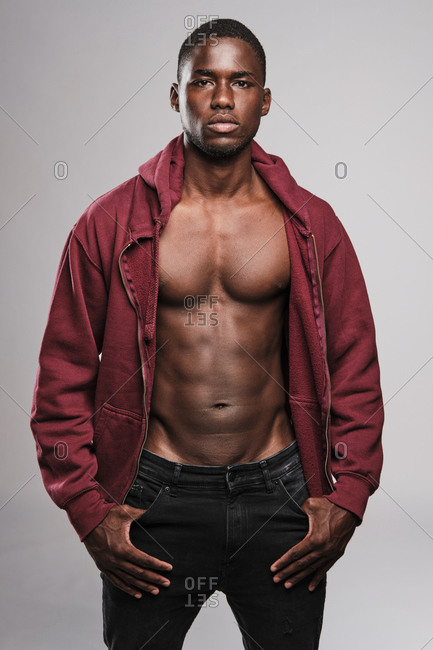 Black fitness man wearing a red hoodie and black trousers standing tall