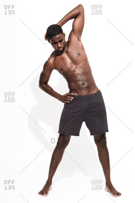 Bare chested black fitness man stretching