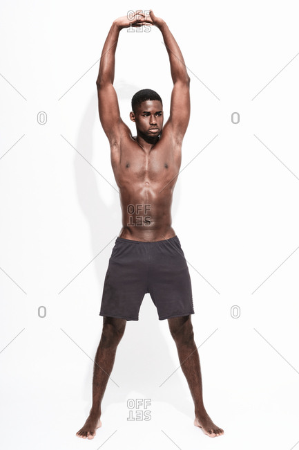 Bare chested black fitness man wearing sport short trousers doing stretching