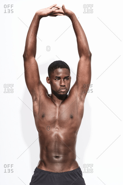 Close up of a bare chested black fitness man wearing sport short trousers doing stretching
