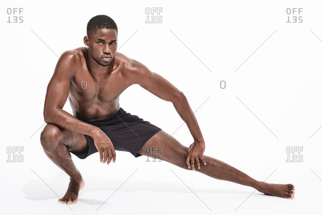 Bare chested black fitness man looking at camera wearing sport short trousers stretching his legs