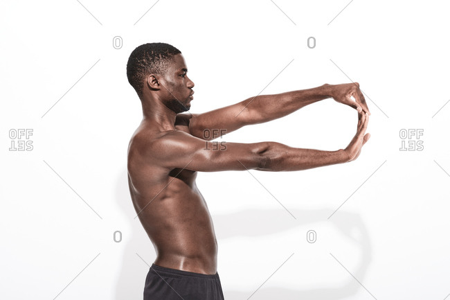 Side view of a bare chested black fitness man wearing sport trousers stretching his arms