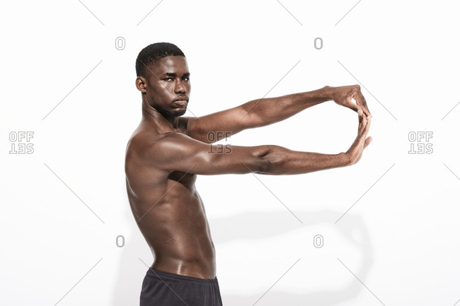 Bare chested black fitness man wearing sport trousers stretching his arms