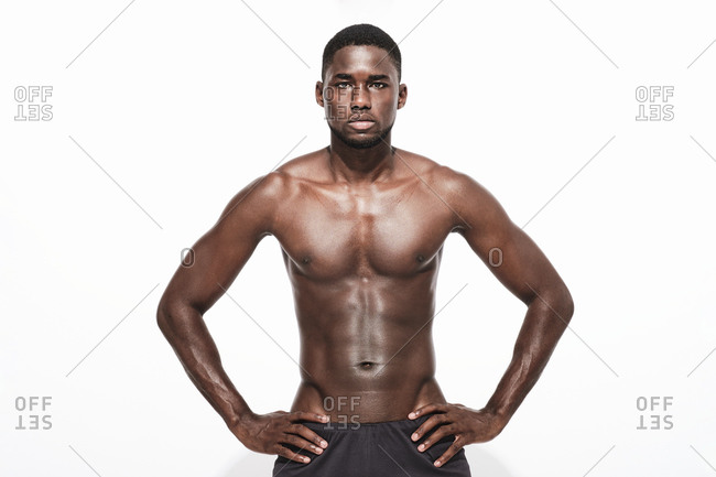 Bare chested black fitness man looking at camera wearing sport short trousers and posing his hands on his hips