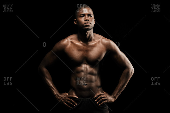 Bare chested black fitness man looking to his left wearing sport short trousers and posing his hands on his hips