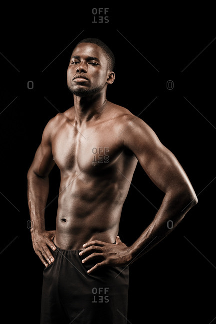 Shirtless black fitness man wearing sport short trousers and posing his hands on his hips