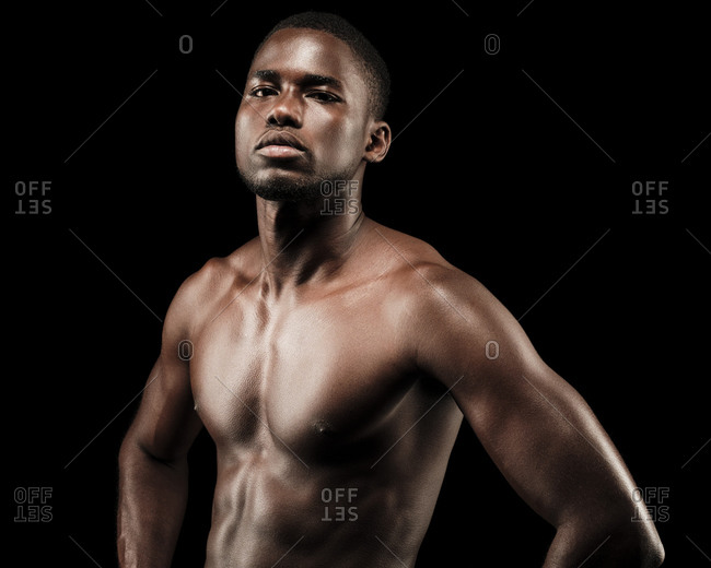 Close up of a shirtless black fitness man wearing sport short trousers and posing his hands on his hips