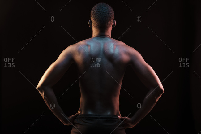 Rear view of standing black man showing his back lit with colored lights