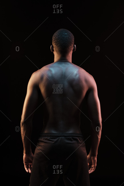 Back view of standing black man showing his back lit with colored lights