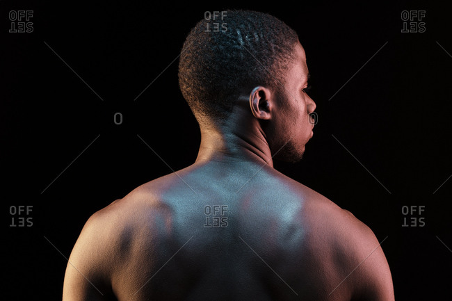 Black man showing his back looking to his right lit with colored lights