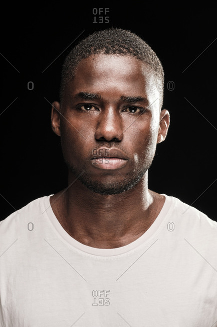 Close up portrait of a black man looking at camera wearing a white t-shirt
