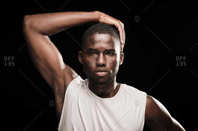 Black man looking at camera wearing a white t-shirt with his hand over his head