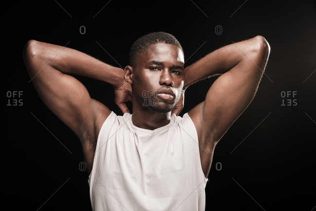 Black man looking at camera wearing a white t-shirt with his hands on his neck