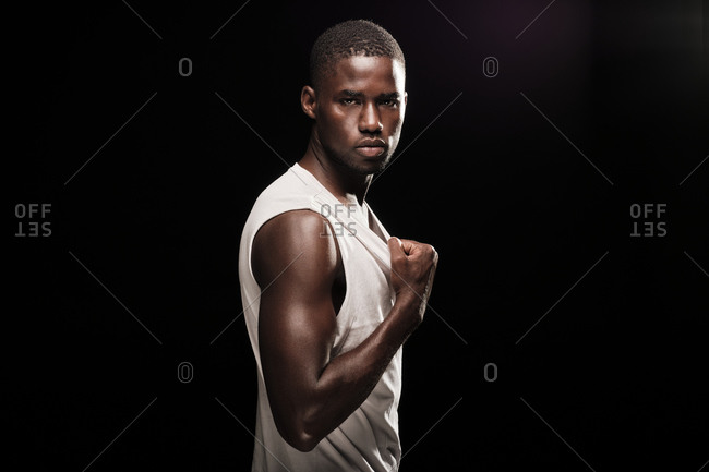 Black man looking at camera wearing a white shirt and stretching his t-shirt