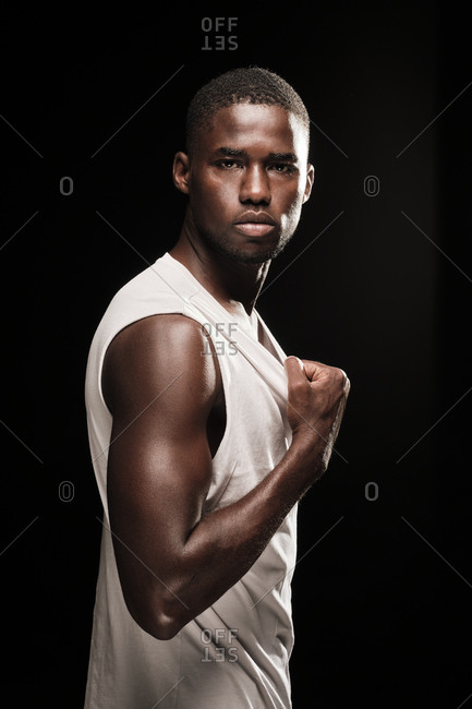 Young black man looking at camera wearing a white shirt and stretching his t-shirt