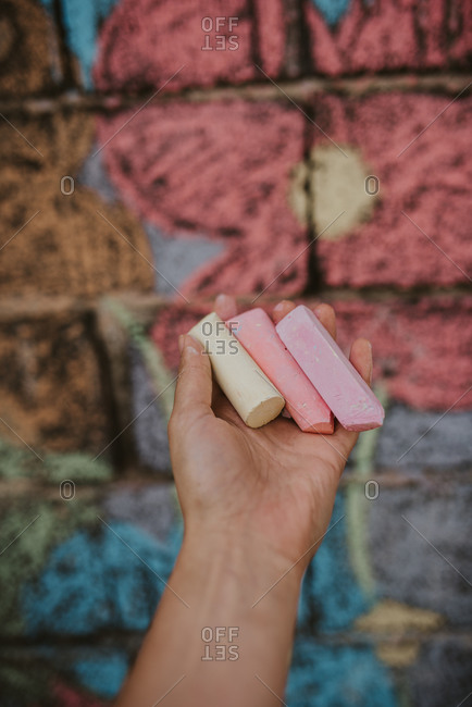 Hand holding three pieces of chalk