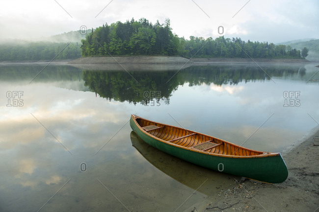 Wood and canvas canoe at sunrise at Sugar Hill Reservoir in Goshen, Vermont