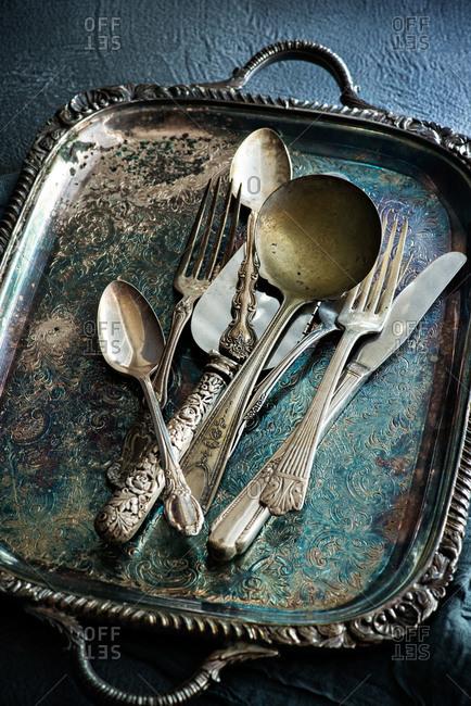 Vintage flatware on antique serving tray over dark rustic background