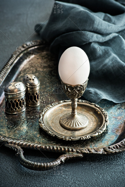 White egg in vintage metal cup over rustic metal serving tray on a grey background