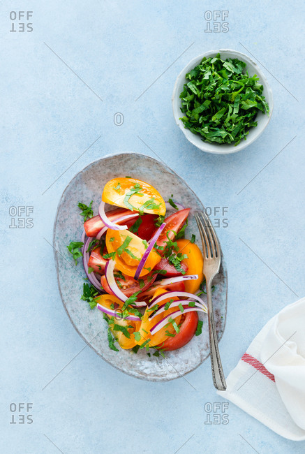 Heirloom tomato salad with olive oil on plate, top view
