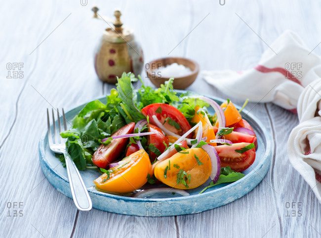 Colorful heirloom tomato salad with kale on blue plate with napkin on the side