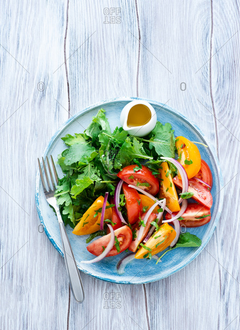 Colorful heirloom tomato salad with kale on blue plate, olive oil dressing on the side