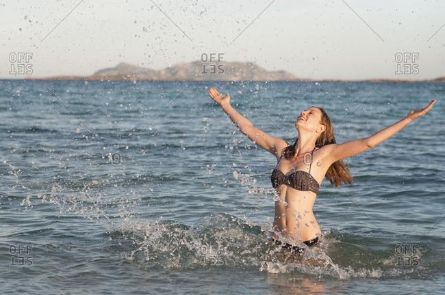 Happy woman in bikini standing in the sea splashing with water- Sardinia- Italy