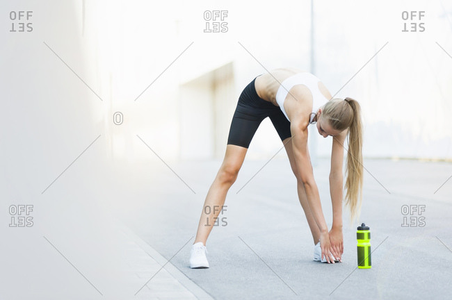 Female jogger stretching her legs in the city