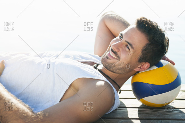 Portrait of smiling young man with ball lying on jetty in front of a lake