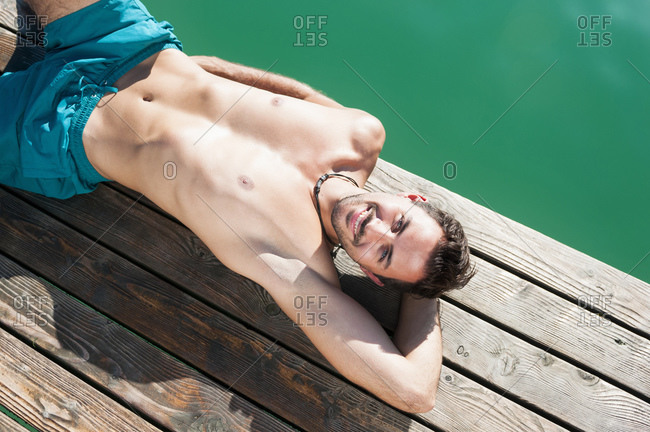 Portrait of smiling young man in swimming shorts sunbathing on jetty