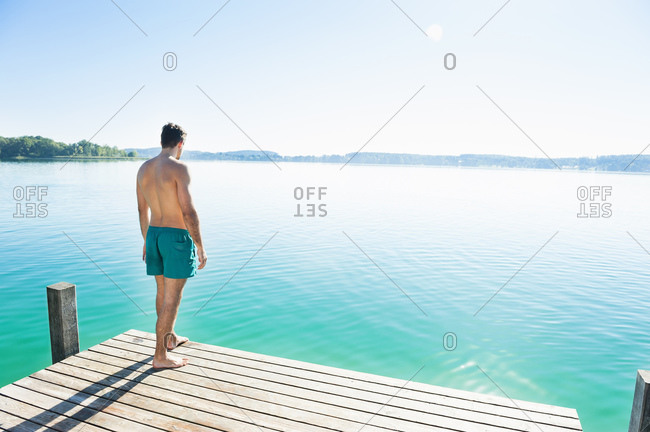 Back view of young man in swimming shorts standing on jetty looking at lake