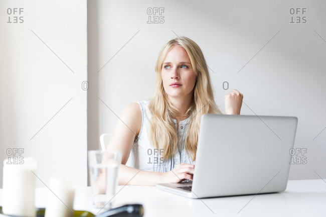 Portrait of blond young woman sitting at table with laptop