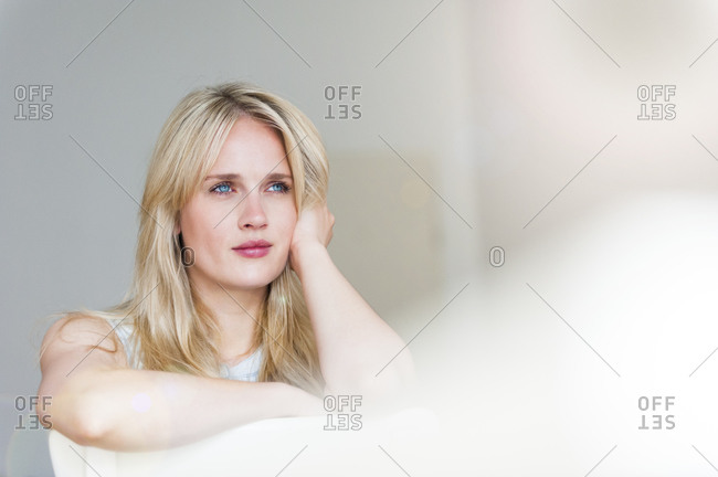 Portrait of pensive blond woman with blue eyes leaning on back rest