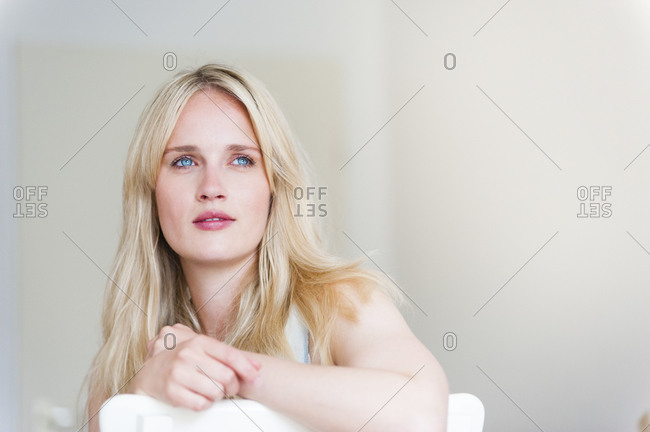 Portrait of blond woman leaning on back rest looking at distance