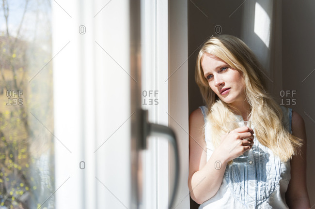 Portrait of serious blond woman looking out of window