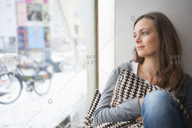 Portrait of daydreaming woman in a coffee shop looking through window in winter