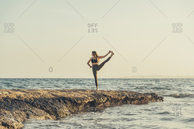 Mature woman practicing yoga at rocky beach in the evening