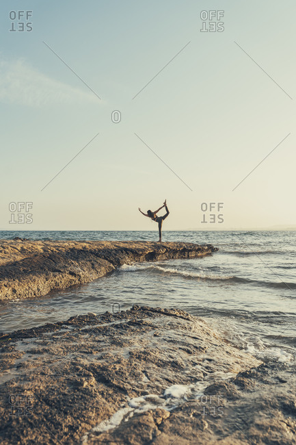 Mature woman practicing yoga at rocky beach in the evening- dancer position