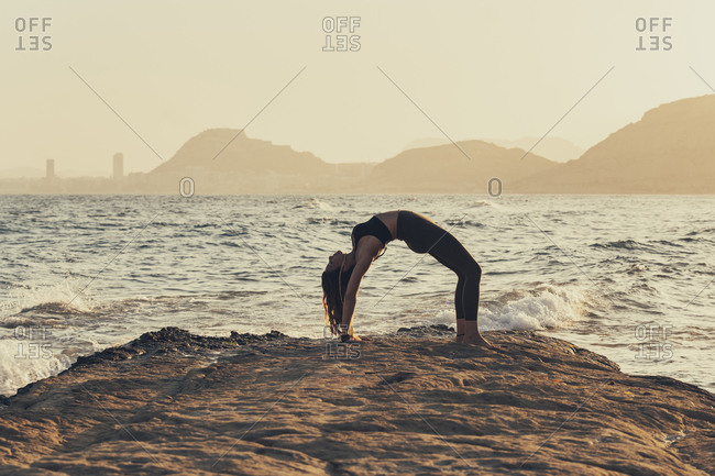 Mature woman practicing yoga at rocky beach in the evening- bow pose