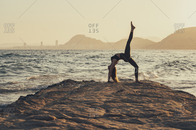 Mature woman practicing yoga at rocky beach in the evening- Urdhva Dhanurasana
