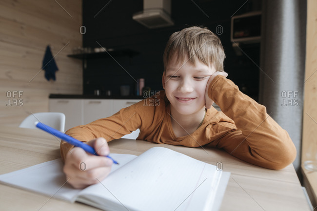 Smiling boy sitting at table writing into booklet at home