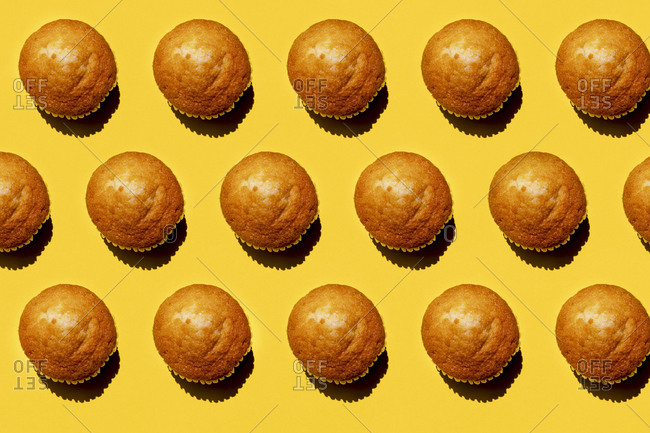 Pattern of rows of muffins against yellow background