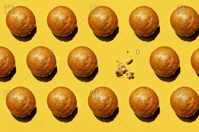Pattern of rows of muffins against yellow background with single one missing