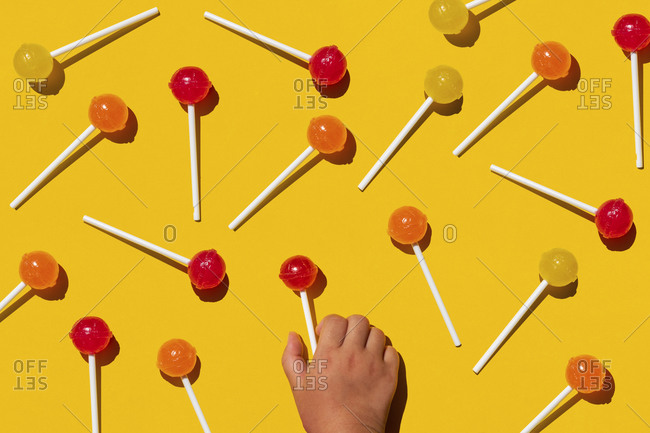 Studio shot of hand of baby girl picking up one of lollipops lying against yellow background